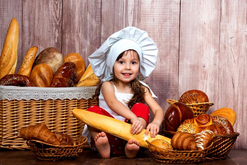 Cute little smiling girl in a chef`s cap sitting with a baguette in her hands near the wicker basket with bread rolls and bakery stock image