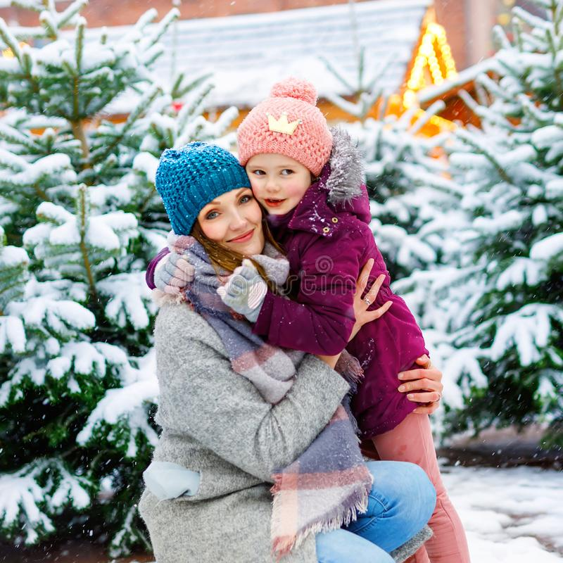 Cute little smiling kid girl and mother on christmas tree market. Happy child, daughter and woman in winter clothes stock images