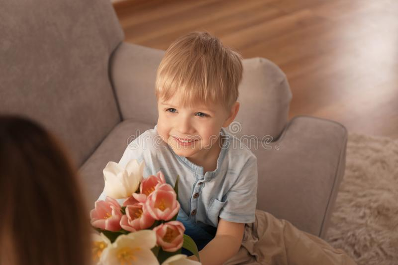 Cute little son giving flowers to his mother at home royalty free stock photos