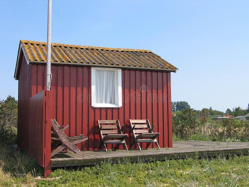 Cute little summerhouse. Cute little red summerhouse by the sea royalty free stock photo