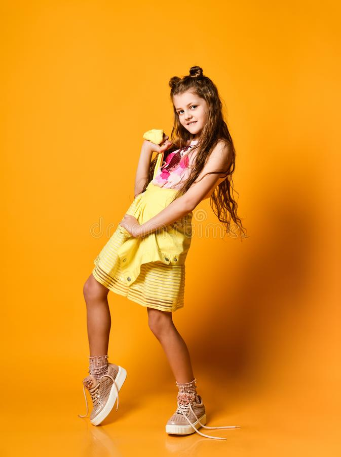 Cute little teen girl in a stylish skirt and jacket clothes looking at the camera and smiling against a yellow studio wall. stock photo
