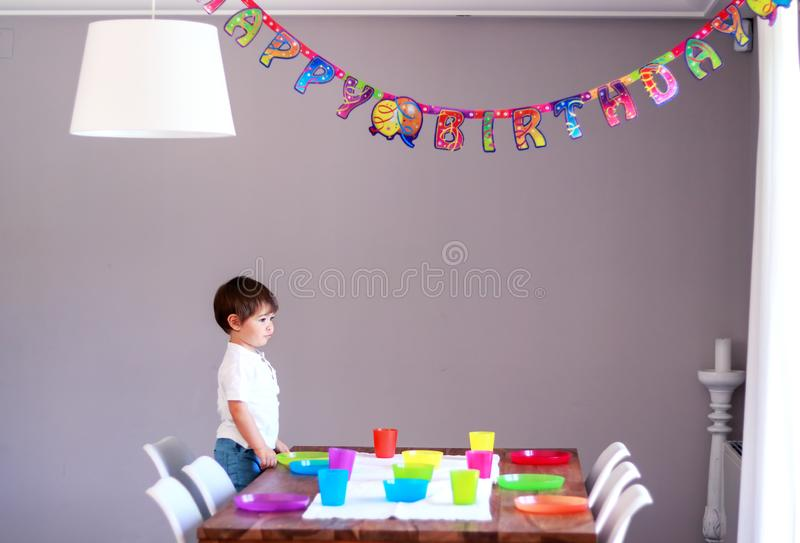 Cute little thoghtful boy setting up table with colorful cutlery preparing to children birthday party. Happy birthday string decor royalty free stock image