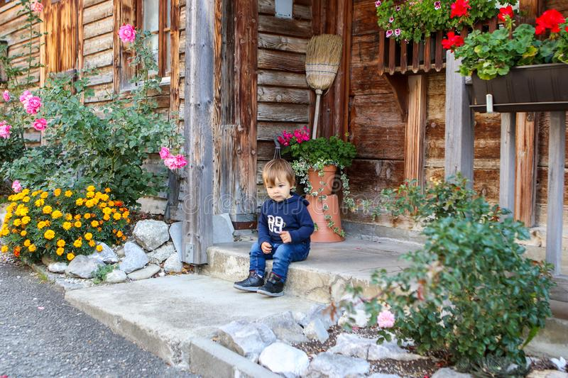 Cute little thoughtful boy sitting on the front porch of old vintage wooden house surrounded by flowers. stock photo