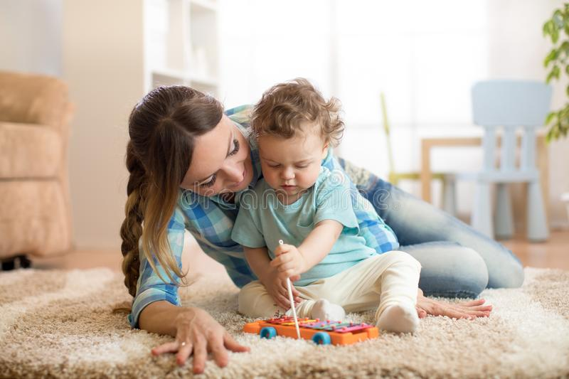 Cute little boy and babysitter playing with toy by the home stock photography
