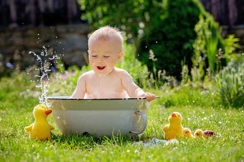 Cute little toddler boy in a basin, taking a bath in garden with. Bubbles and duck toys, smiling happily stock photography