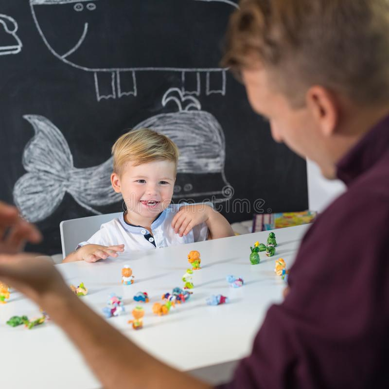 Cute little toddler boy at child therapy session. Cute little playfull toddler boy at child therapy session. Private one on one homeschooling with didactic aids stock photo