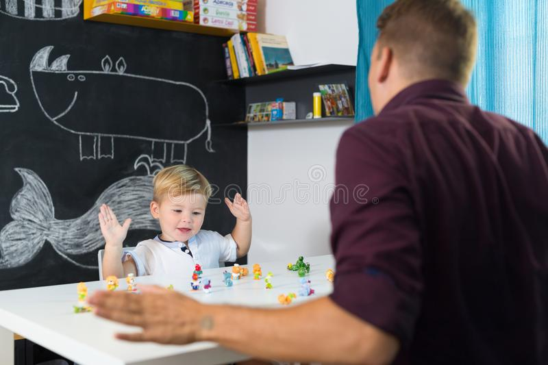 Cute little toddler boy at child therapy session. Cute little playfull toddler boy at child therapy session. Private one on one homeschooling with didactic aids royalty free stock image
