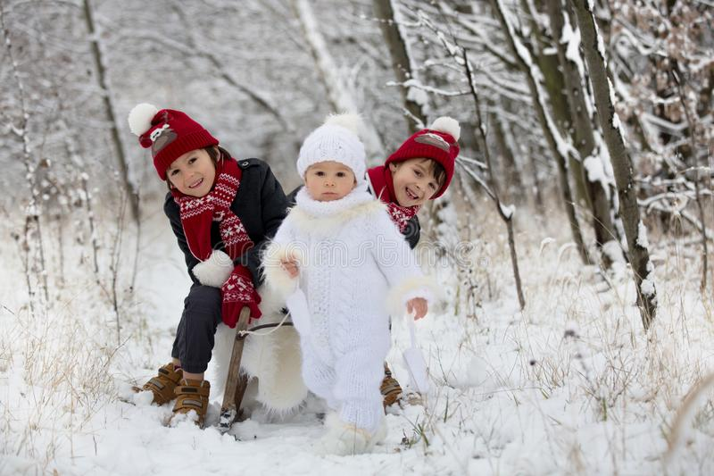 Cute little toddler boy and his older brothers, playing outdoors with snow on a winter day royalty free stock images