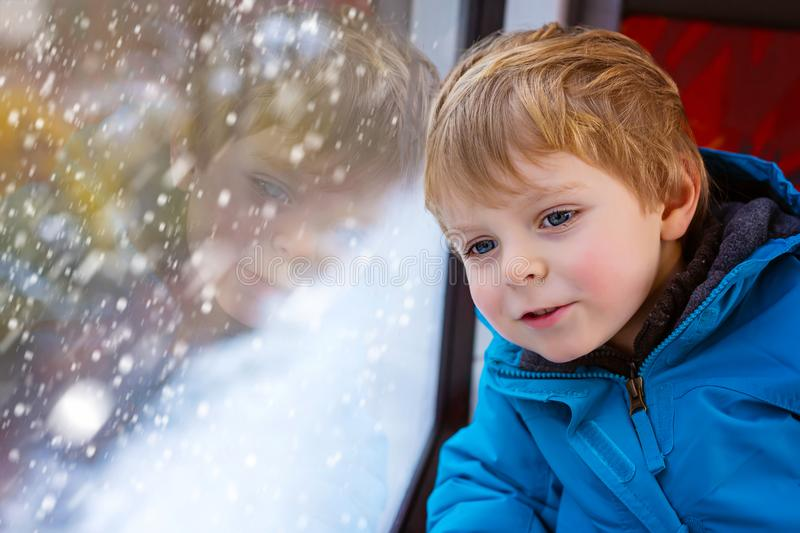 Cute little toddler boy looking out train window. Happy cute little toddler boy looking out through window of a train, while it moving. funny adorable kid stock image
