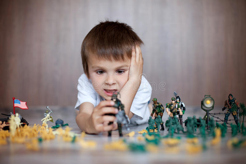 Cute little toddler boy, playing at home with soldiers and figurine toys stock image