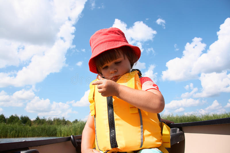 Cute little toddler boy sitting in canoe in the lake. Portrait of cute little toddler boy in yellow life vest and red hat sitting in canoe and looking seriously stock image