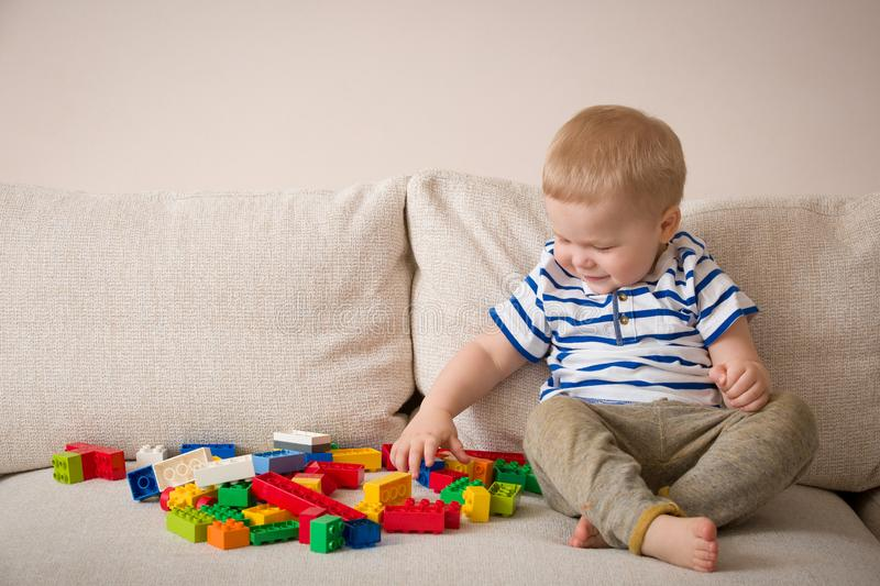 Cute little toddler boy in a striped shirt playing colorful plastic blocks on the sofa indoors. child having fun stock image