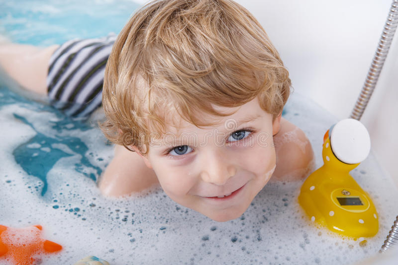 Cute little toddler boy of two years having fun by taking bath i stock photo