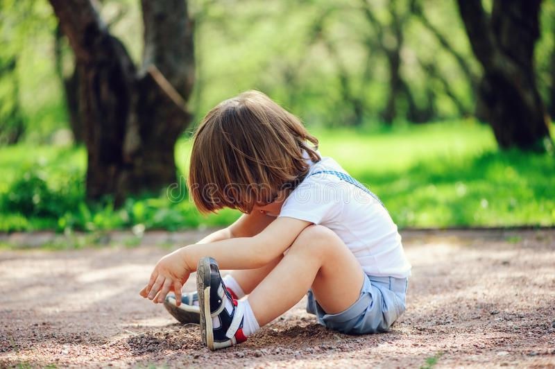 cute little toddler child boy playing with dirt and sitting on the ground stock photos
