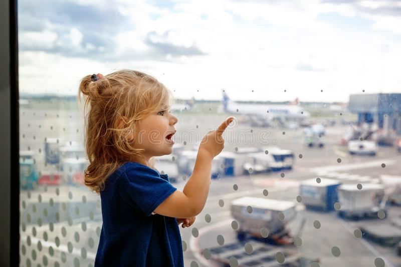 Cute little toddler girl at the airport, traveling. Happy healthy child waiting near window and looking at planes royalty free stock images