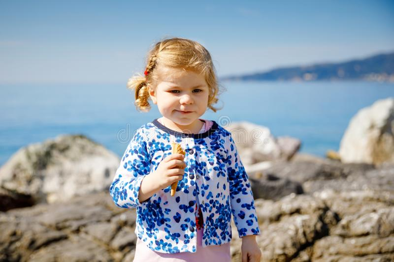 Cute little toddler girl eating ice cream in cone on family vacations. Happy healthy baby child with icecream waffle royalty free stock photos