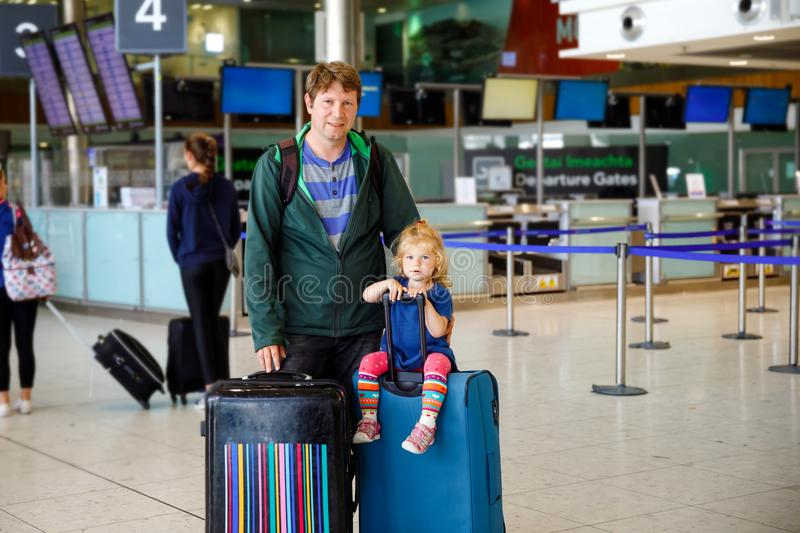 Cute little toddler girl and father at the airport. Happy family traveling by plane, making vacations. Young dad and. Baby daughter with suitcases waiting for stock photos