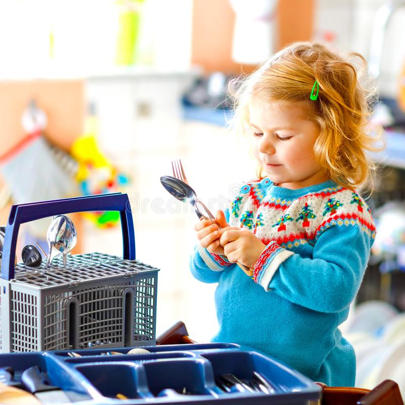 Cute little toddler girl helping in the kitchen with dish washing machine. Happy healthy blonde child sorting knives. Forks, spoons, cutlery. Baby having fun royalty free stock image