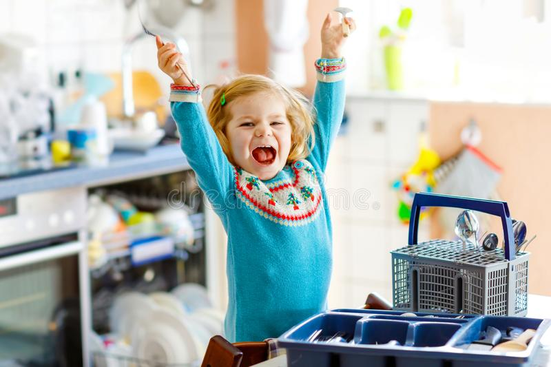 Cute little toddler girl helping in the kitchen with dish washing machine. Happy healthy blonde child sorting knives. Forks, spoons, cutlery. Baby having fun royalty free stock photography