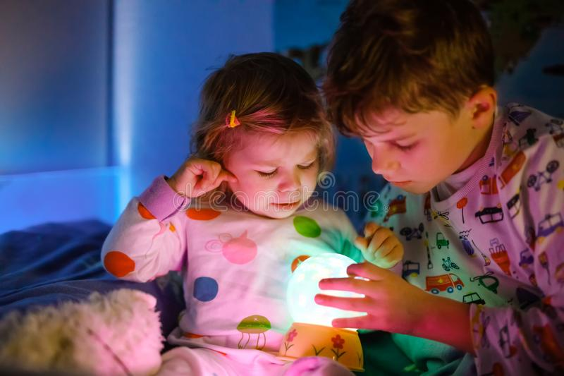 Cute little toddler girl and kid boy playing with colorful night light lamp before going to bed. Sleepy tired baby stock image