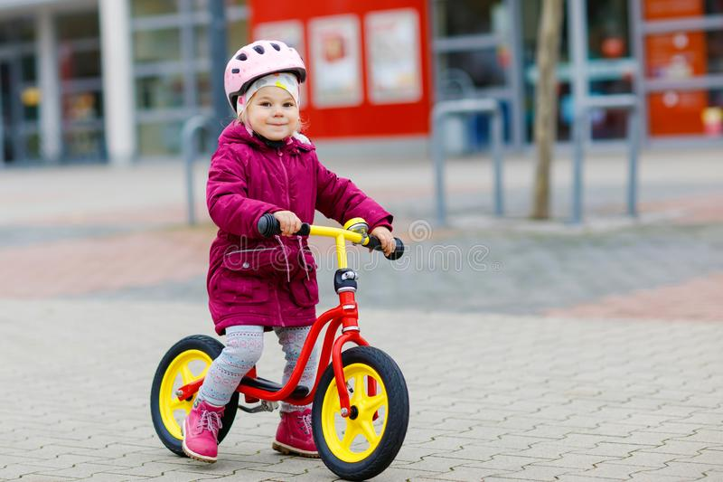 Cute little toddler girl in safety helmet riding on run balance bike. Happy healthy lovely baby child having fun with stock image