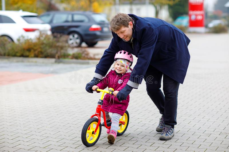 Cute little toddler girl in safety helmet riding on run balance bike. Middle-aged father teaching happy healthy lovely stock photos