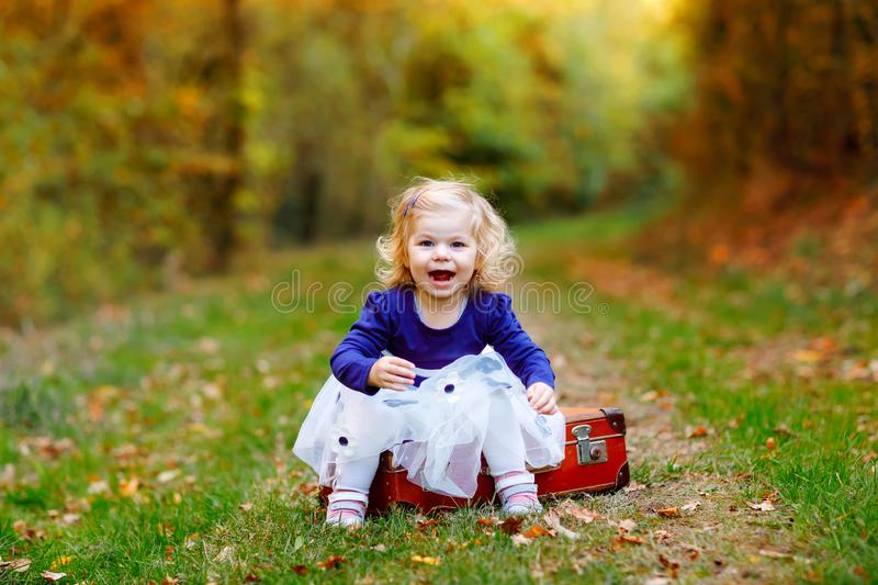 Cute little toddler girl sitting on suitcase in autumn park. Happy healthy baby enjoying walking with parents. Sunny royalty free stock photos