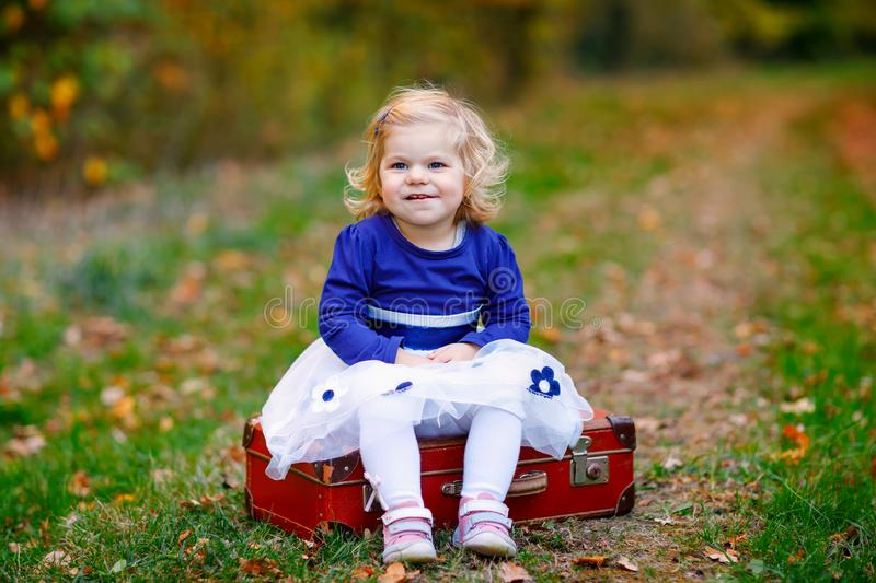 Cute little toddler girl sitting on suitcase in autumn park. Happy healthy baby enjoying walking with parents. Sunny. Warm fall day with child. Active leisure stock photos
