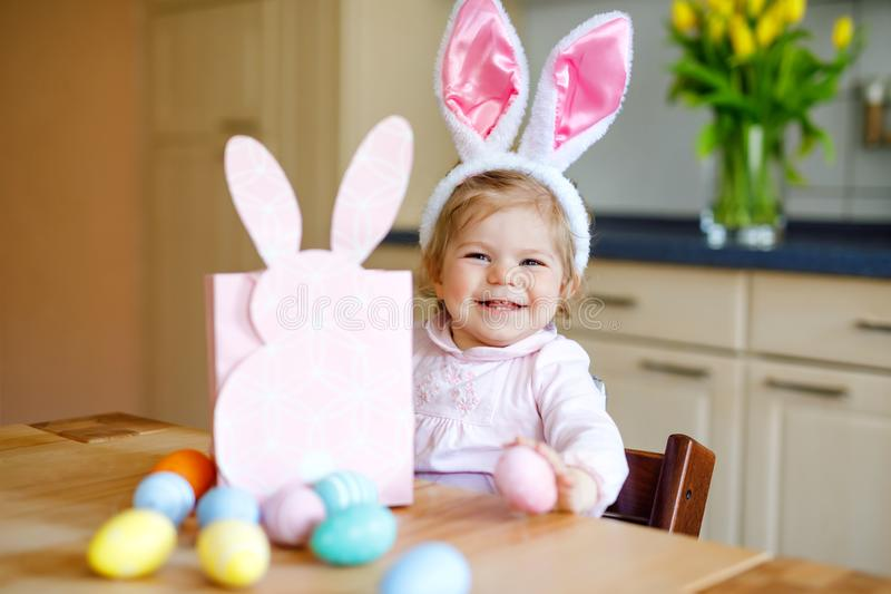 Cute little toddler girl wearing Easter bunny ears playing with colored pastel eggs. Happy baby child unpacking gifts stock photo