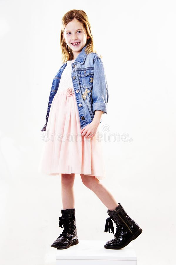 Cute little trendy girl is posing to the camera. stock photo