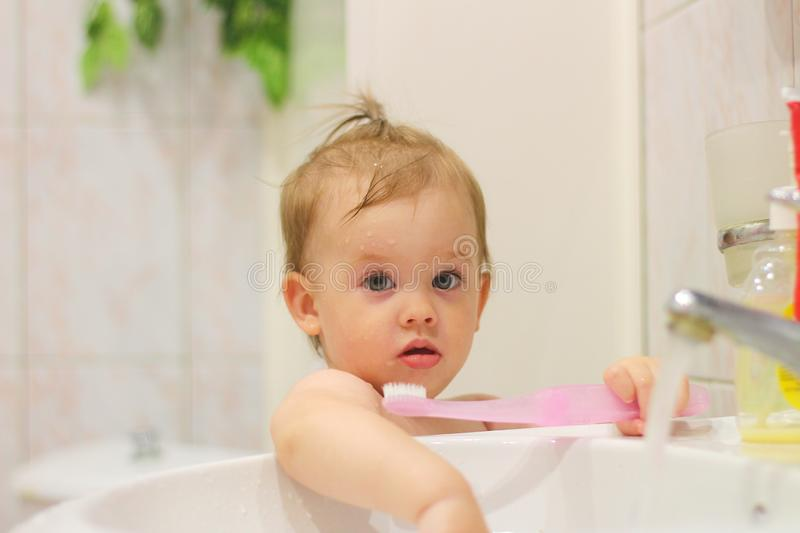 Cute little white child with a tail brushes his teeth near the washbasin. Joy, cheerful, small, oral, water, boy, paste, blond, blonde, cleaning, adorable royalty free stock photography