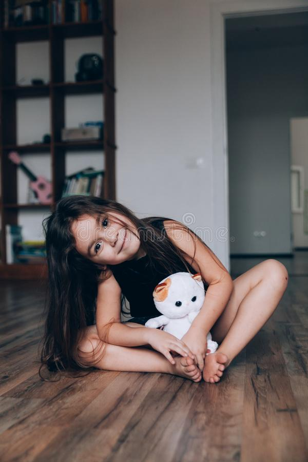 Cute little 5-year girl sitting on the floor hugging toy stock photos