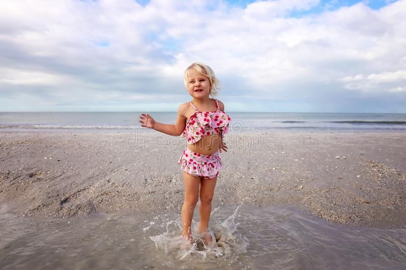 Cute Little Child Splashing and Playing in the Water on the Beach by the Ocean stock image