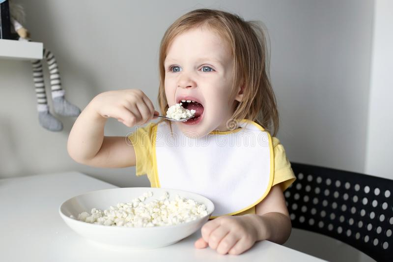 Cute little 2 years girl eats quark royalty free stock photography