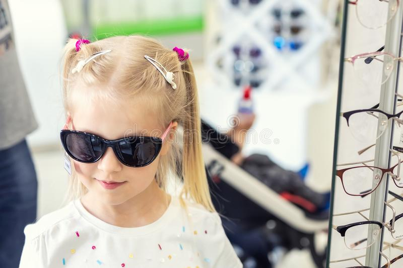 Cute little young caucasian blond girl trying on and choosing sunglasses in front of mirror at optic eyewear store. Adorable. Schoolgirl child having fun bying royalty free stock photo