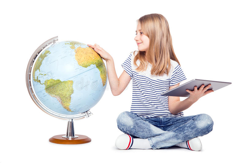 cute little young girl with tablet and globe. Schoolgirl using modern technology in teaching geography royalty free stock photo