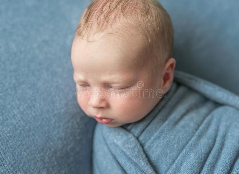 Cute llitle baby in hat covered with blue blanket sleeping royalty free stock images