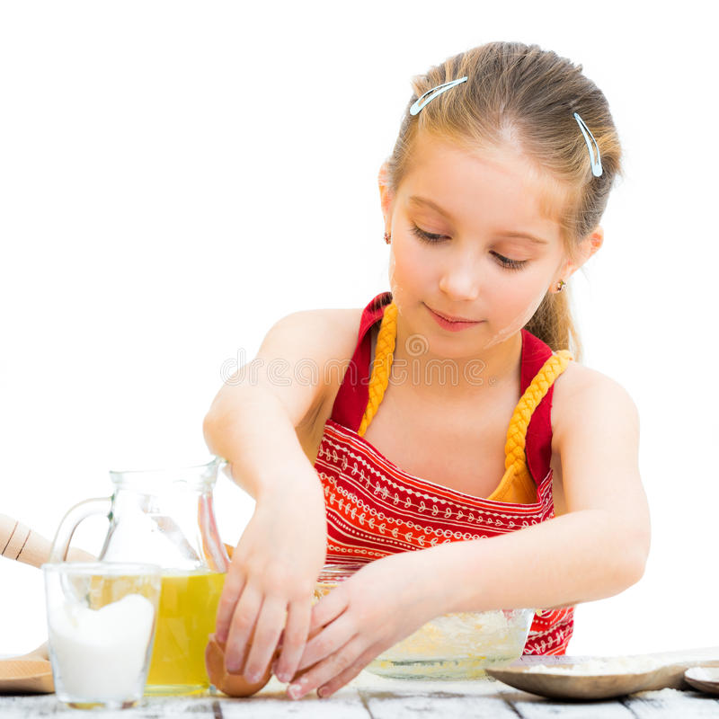 Cute llittle girl cooking. Isolated on a white background royalty free stock images