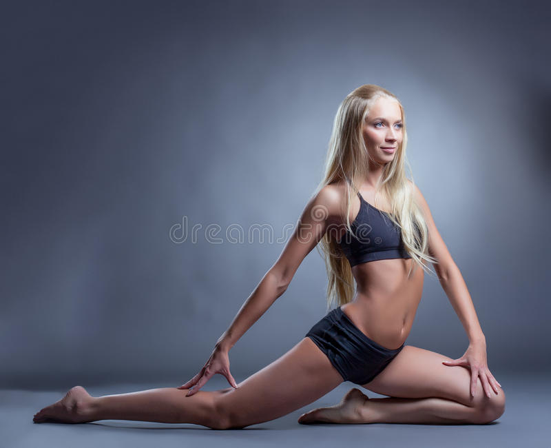 Cute long-haired blonde doing stretching exercises royalty free stock photo