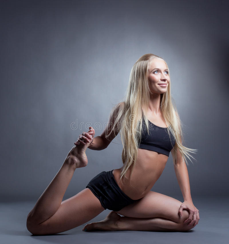 Cute long-haired blonde doing stretching royalty free stock photos