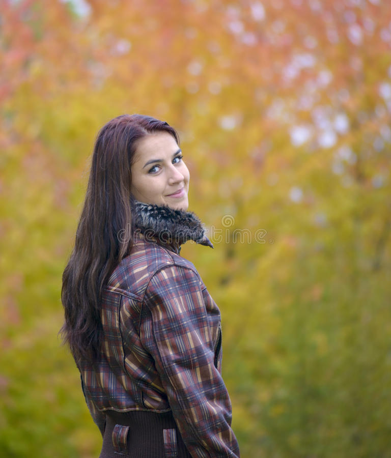 Cute long haired brunette girl. In autumn time royalty free stock photo