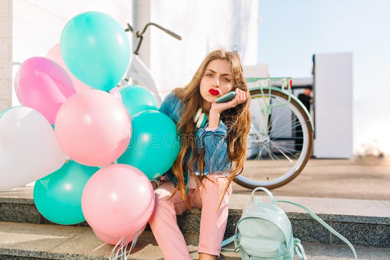 Cute long-haired girl with face expression of discontent waiting for friends who are late, holding helium balloons stock photo