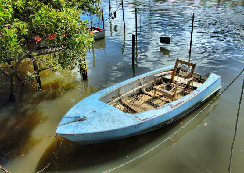 A small blue boat with a chair has seen better days. A cute looking small blue boat with a wooden chair looks like a good spot for relaxing royalty free stock photos