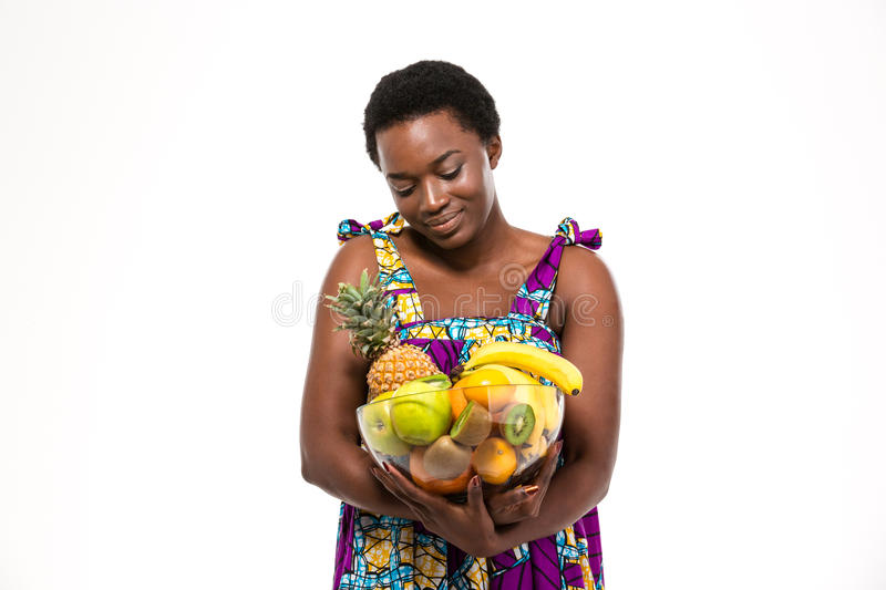Cute lovely african woman holding glass bowl with different fruits royalty free stock photos