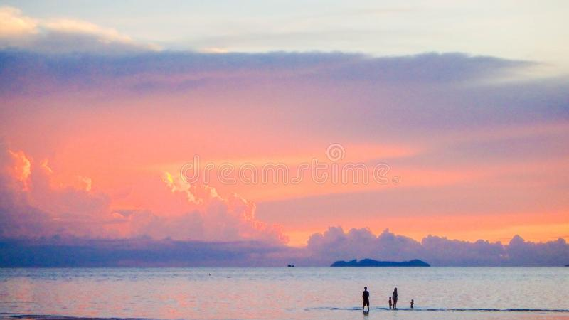 Cute lovely family walking on beach beautiful pastel sunset. Background royalty free stock photo