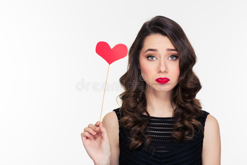 Cute lovely sad curly girl holding heart booth royalty free stock images