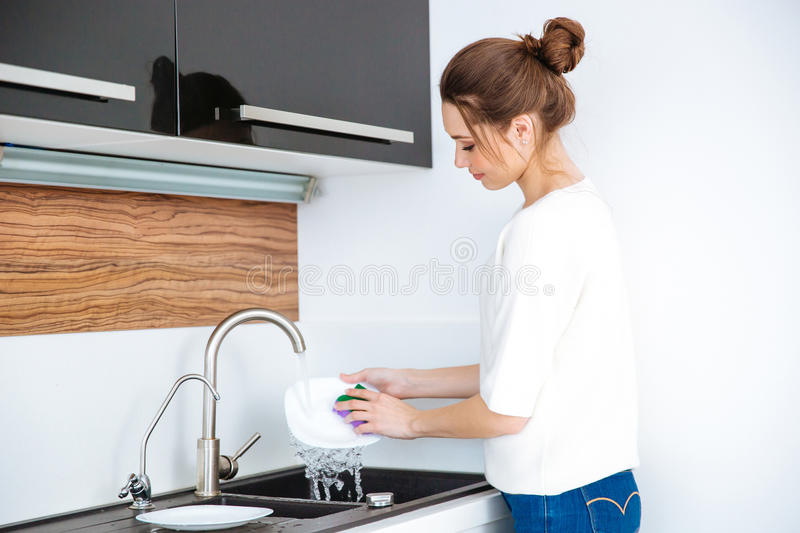 Cute lovely woman standing and washing dishes stock images