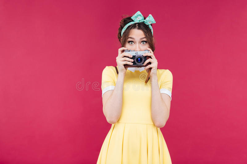 Cute lovely young woman covered her face with old camera stock images