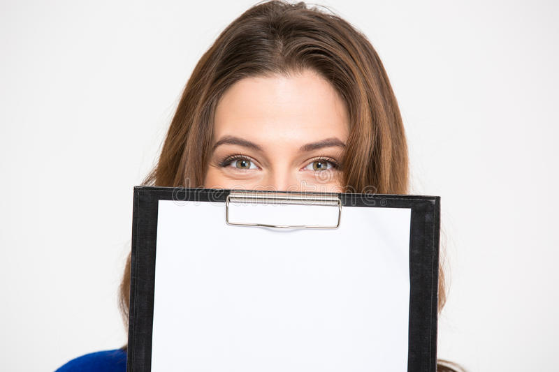 Cute lovely young woman hiding behind blank clipboard stock photos