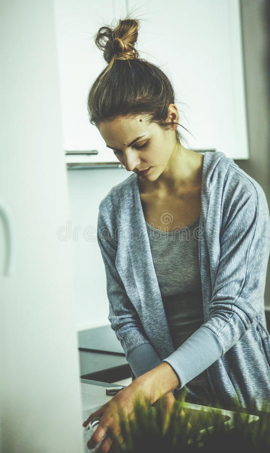 Cute lovely young woman standing and washing dishes royalty free stock photos